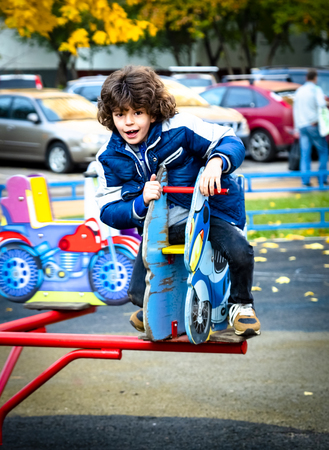 Little boy having fun with carousel on outdoor playground. Spring or autumn active sport leisure for kids. Kindergarten or school yard. Toddler child activity