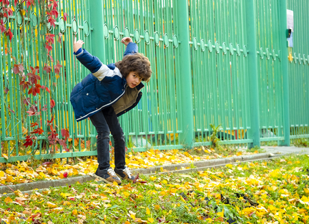 Fashionable little boy posing near green iron fence in autumn cold day.The child is trying to jump from a slide. Standard-Bild