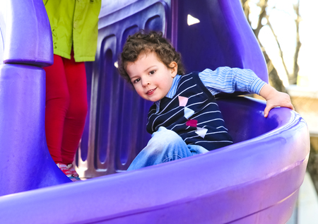 boy having fun sliding down on the playground. kid playing outdoors. copy space for your text Zdjęcie Seryjne
