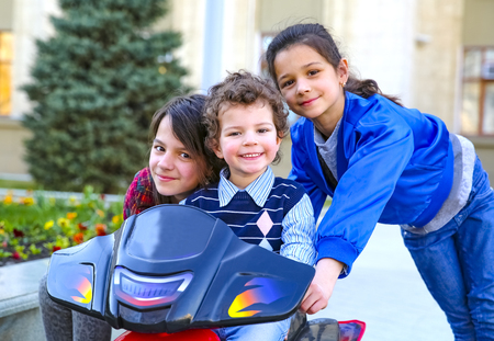 Kids driving electric toy car in summer park. Outdoor toys. Children in battery power vehicle. Little boy and his two older sisters are riding a toy truck in the city. Affection and fun time concept Stock Photo