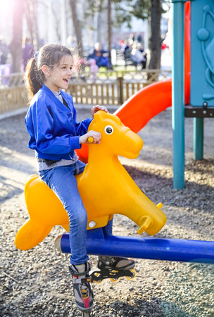 Little girl swinging on a plastic yellow horse. The concept of a happy childhood, games in the city park, in kindergarten and in the family.