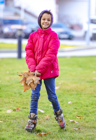 happy little child, sweet girl laughing and holding yellow leaves in the autumn city park walk outdoors Archivio Fotografico