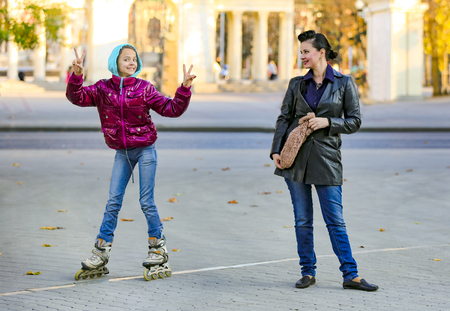 Mom and her daughter for a walk. Teenage girl in red jacket roller skating at street and showing victory gesture on the background of the autumn city Zdjęcie Seryjne