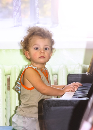 Little boy plays the brown piano on notes.