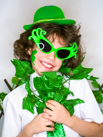 Child Celebrating St. Patrick's Day Showing his Make-up. A small, curly smiling boy in green carnival accessories looking at the camera. green background Banco de Imagens - 118655420