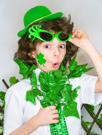 Funny St Patricks day little curly boy wearing a green hat and green carnival accessories shocked with an open mouth. light background Фото со стока