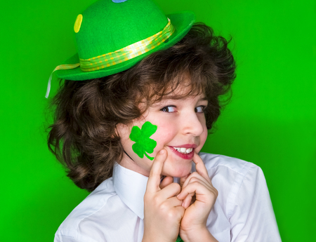 Child Celebrating St. Patricks Day Showing his Make-up. A small curly boy in green carnival accessories points his fingers at a drawing in the form shamrock on his cheek.green background Banco de Imagens