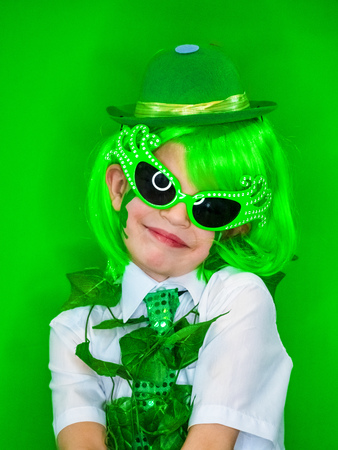 Child Celebrating St. Patricks Day Showing his Make-up. A small smiling boy in green carnival accessories looking at the camera. green background