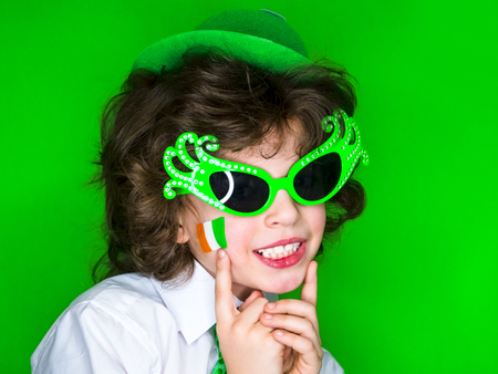 Child Celebrating St. Patricks Day Showing his Make-up. A small, curly boy in green carnival accessories points his finger at Irish flag on his cheek. green background