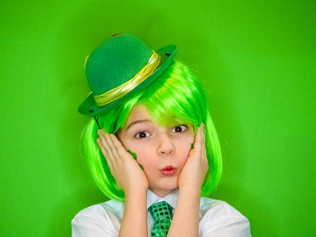 A dreaming cute boy is holding his head on his hands Celebrating St. Patrick's Day. A small child in green carnival accessories looking at the camera. green background Banco de Imagens - 118655482