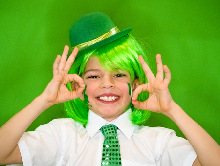 Child Celebrating St. Patricks Day Showing his Make-up. A small, curvy boy with shamrock and Irish flag on his cheeks showing a gesture okay. slow motion. green background