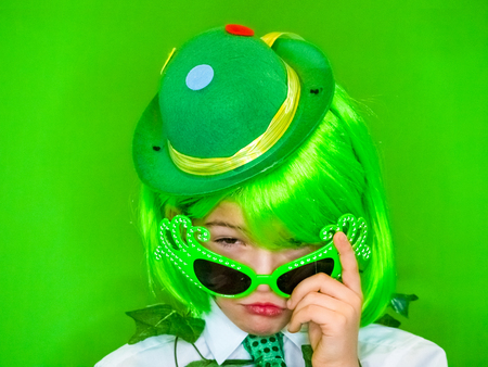 Child Celebrating St. Patricks Day looks suspiciously over his glasses. A small boy in green carnival accessories looking at the camera. green background