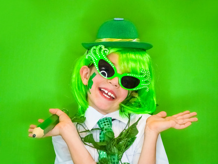 Funny St Patricks day stunning little boy wearing a green hat, carnival glasses and a tie. Cute child posing with a big green pencil in his hands