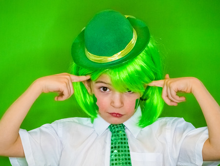 Child Celebrating St. Patrick's Day Showing his Make-up. A small cute boy in green carnival accessories looking at the camera.Young boy with the index fingers on his head green background Фото со стока