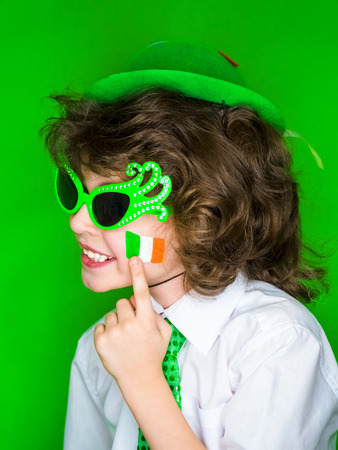 Child Celebrating St. Patrick's Day Showing his Make-up. A small, curly boy in green carnival accessories points his finger at Irish flag on his cheek. green background Banco de Imagens - 118655499