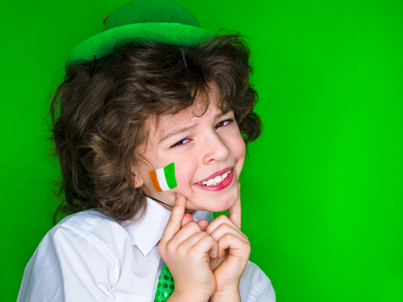 Child Celebrating St. Patrick's Day Showing his Make-up. A small, curly boy in green carnival accessories points his finger at Irish flag on his cheek. green background Banco de Imagens - 118655502