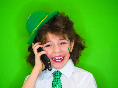 Funny St Patricks day little boy wearing a green hat and shamrock, the Irish flag on his cheeks talking on the phone. A child listening to good news on the phone is incredibly excited and joyful Banque d'images - 118655527