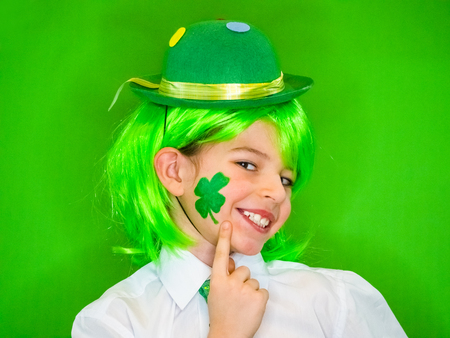 Child Celebrating St. Patrick's Day Showing his Make-up. A small, boy in green carnival wig points his finger at a drawing in the form shamrock on his cheek.green background