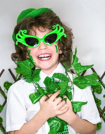 Child Celebrating St. Patrick's Day Showing his Make-up. A small, curly smiling boy in green carnival accessories looking at the camera. green background Banco de Imagens - 118655536