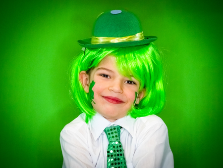 Child Celebrating St. Patrick's Day Showing his Make-up. A small smiling boy in green carnival accessories looking at the camera. green background Banco de Imagens - 118655546