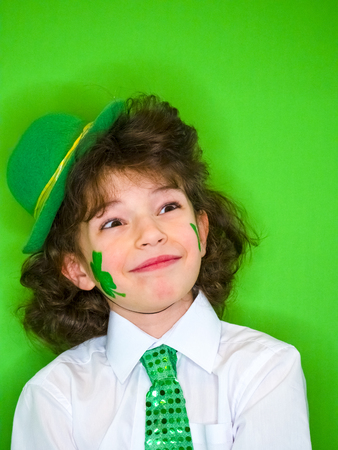 Charming child boy having fun during Saint Patrick celebrations over a green background. Little boy with shamrock on his cheek. A child looking up. Patricks Day celebrations. Banco de Imagens