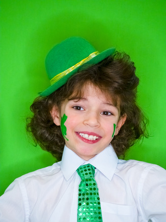 Hispanic child boy having fun during Saint Patrick celebrations over a green background. A little boy with a green shamrock and irish flag on his cheeks. Patricks Day celebrations.