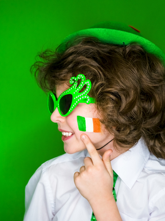 Child Celebrating St. Patrick's Day Showing his Make-up. A small, curly boy in green carnival accessories points his finger at Irish flag on his cheek. green background