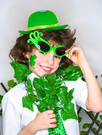Child Celebrating St. Patrick's Day Showing his Make-up. A small, curly smiling boy in green carnival accessories looking at the camera. green background Banco de Imagens - 118655575