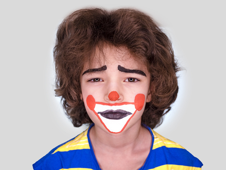 little cute boy with facepaint like clown, pantomimic expression. April Fool's Day, April 1. Isolated on gray