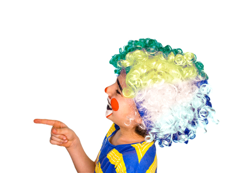 the boy in the bright multi-colored wig. funny mime poses pointing finger at copy space.Isolated on white background