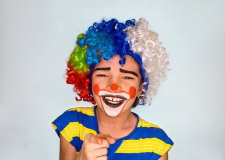 Handsome little boy Laughs and Points Finger. little cute boy with facepaint like clown, pantomimic expression. emotions. April Fool's Day, April 1