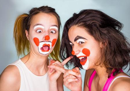 조롱, 조롱 개념. 두 친구가 서로 손가락을 가리키며 웃고 있습니다. 스튜디오 촬영, 회색 배경입니다. 색상 배경에 재미있는 변장을 한 가족. 만우절 기념