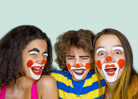 Two teen sisters and a little brother in the role of clowns posing in the studio