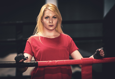 Beautiful sports girl on a street workout. Young beautiful female boxer portrait at gym.light blur