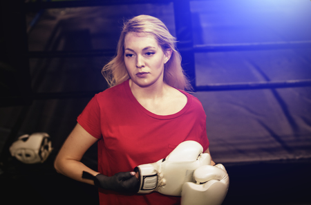 Young pretty boxer woman standing near the ring. The athlete removes white boxing gloves after the fight. light blur