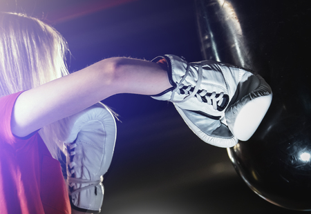 Woman hits the boxing heavy bag in the gym. Hard mixed martial arts training