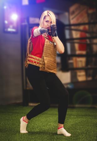 jeune femme blonde avec des ceintures de boxe dans ses mains, l'air déterminé, fort et vif, portant un gilet léger sur fond de salle de sport et de ring de boxe. léger flou Banque d'images