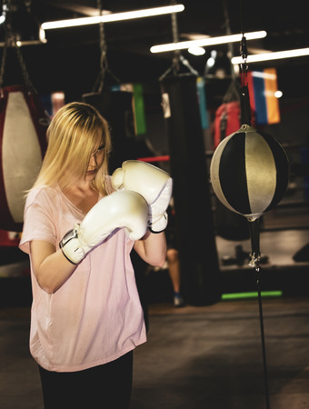 Boxer woman training at the punching ball