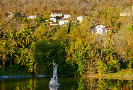 Sukhum, Abkhazia, - 03 January, 2013: Sculpture of archer in the pond and a view of the residential houses and restaurant Gagripsh on a mountainside