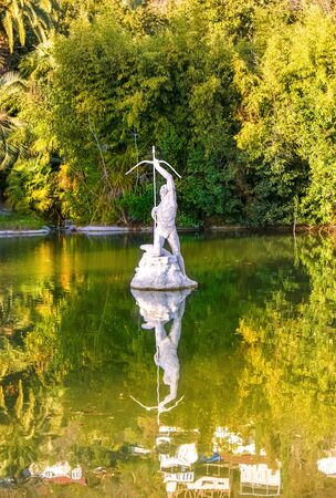 Gagra, Abkhazia, Georgia - January 1, 2013: Sculpture of archer in the pond and a view of the residential houses on a mountainside in Water Reflection