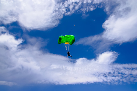 Parachutist in action. paraglider flies over the clean blue sky
