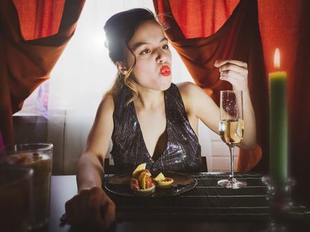 Piękna dziewczyna pijana w restauracji jedząc deser. Oszałamiająca dziewczyna siedzi w kawiarni i pije szampana. Styl vintage. Selektywna koncepcja ostrości. Obżarstwo.