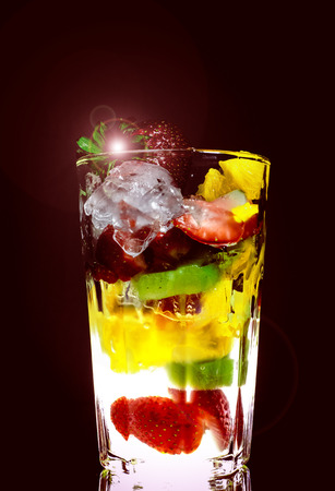 Dessert layered in a transparent glass, mineral water, orange, kiwi, nuts on a dark background. The concept of healthy, proper and simple Healthy food Reklamní fotografie