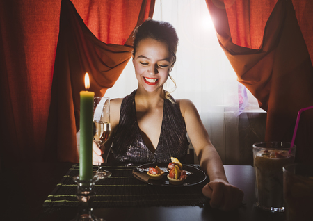 A beautiful girl in a restaurant eating dessert. Stunning girl are sitting in a cafe, laughing and drinking champagne.Vintage style.