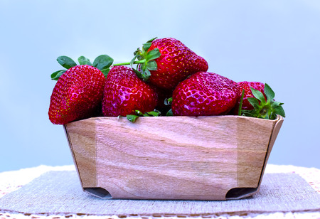 Delicious ripe strawberry in wooden basket on a table covered with a lace tablecloth. Stockfoto