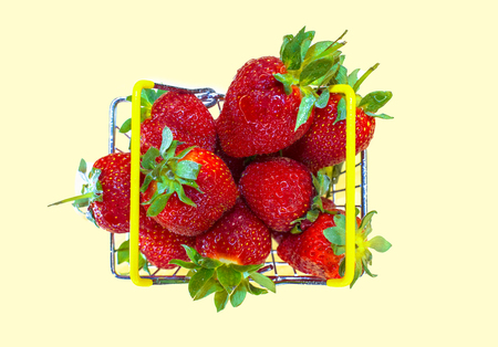 Self-service supermarket shopping basket with fresh strawberries, grocery products on a light background.Top view.