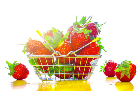 Self-service supermarket shopping basket with fresh strawberries, grocery products on a light background.