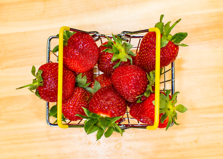 Self-service supermarket shopping basket with strawberries, grocery products on wooden table. Top view.
