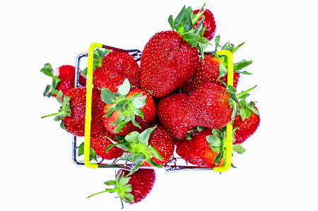 Self-service supermarket shopping basket with fresh strawberries, grocery products on a light background. View from above