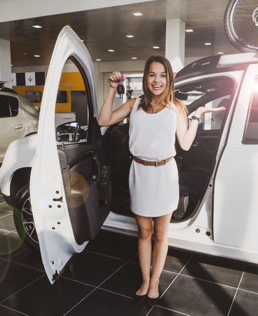 Beautiful positivity girl standing near automobile with opened door in showroom of car center and holding keys in hand. Pretty young woman with chestnut hair smiling and showing new present at camera.